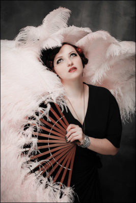 Ruby Bordeaux of Missoula's Cigarette Girls Burlesque Troupe with large pink fan.