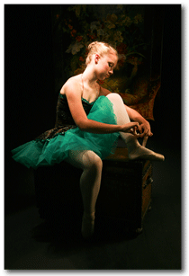Young Ballet Dancer  in beautiful light putting on her point shoes.