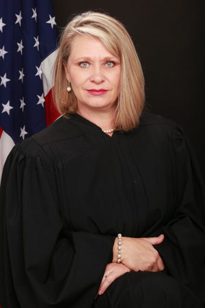 Campaign image of Judge Landee Holloway in studio with lighting and American Flag behind her.