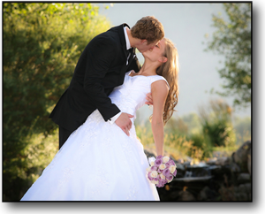 Wedding Photography of groom dipping the bride as he kisses her, outside in beautiful light.