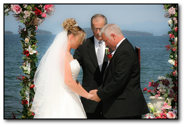 Bride and groom bowed in prayer in front of minister on the shore of a mountain lake.