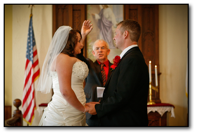 Couple standing at the alter as minster holds ring up blessing it during a Montana Wedding ceremony.