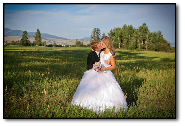 Groom kissing the bride in vast beautiful Western Montana Landscape on a sunny day.